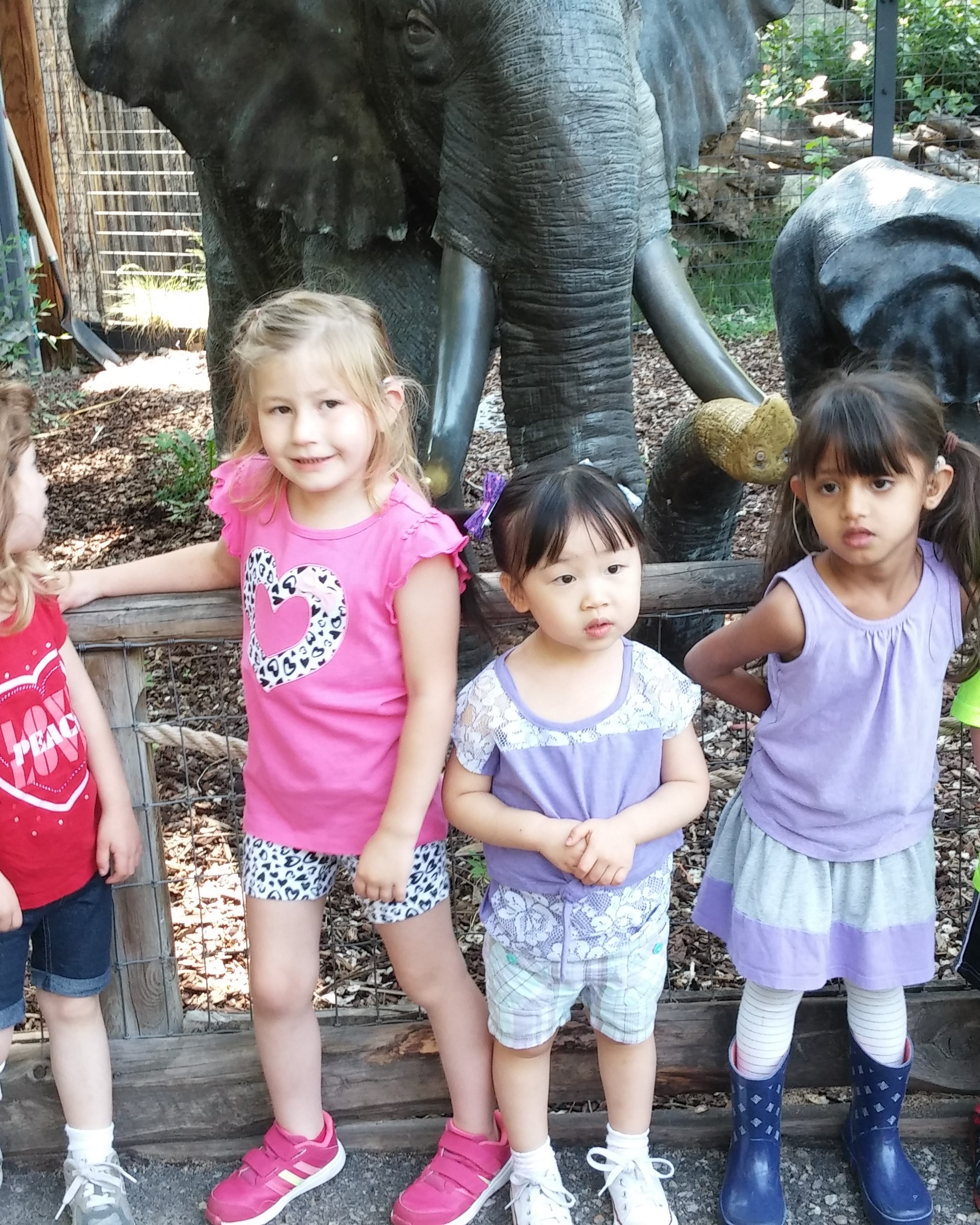 pre-school children posing in front of elephant statue